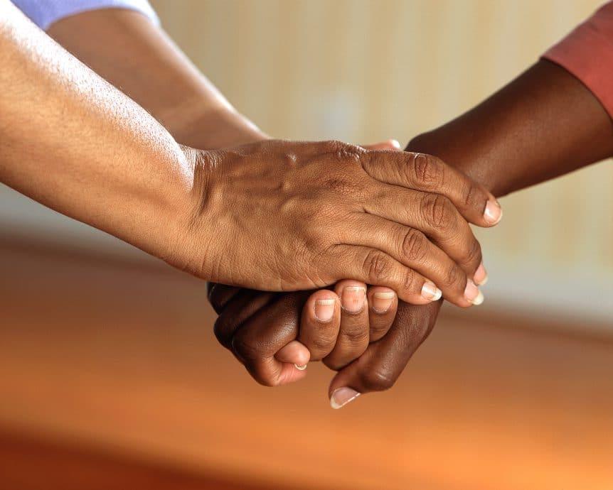 Zwei verschlungene Hände in Großaufnahme symbolisieren die Unterstützung durch eine Testamentsspende
