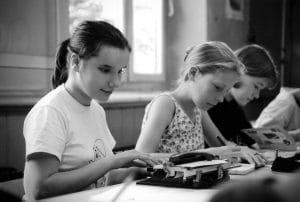 Drei Mädchen mit Braillemaschinen
