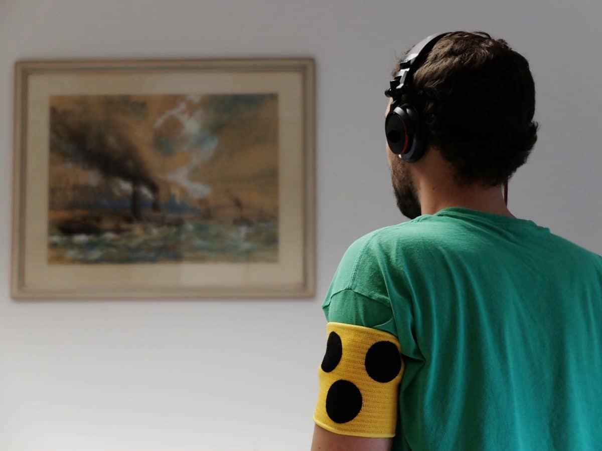 Ein Mann mit Blindenarmbinde und dicken Kopfhörern auf den Ohren steht einem verschwommenen Bild zugewandt.