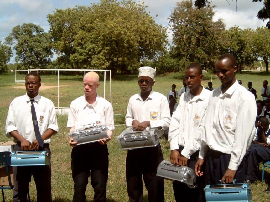 Jugendliche mit Braille-Maschinen in der Hand stehen auf dem Schulhof in Kenia
