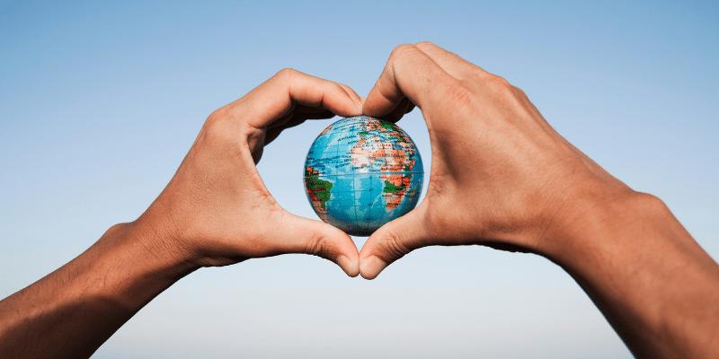 zwei Hände umschließen herzförmig eine Weltkugel